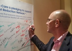 Chief Executive David Cole signing his support for reducing restrictive practice